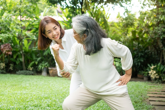 An old elderly asian woman and exercise in the backyard with her daughter.