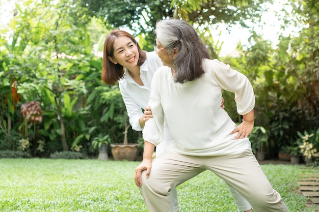 An old elderly asian woman and exercise in the backyard with her daughter