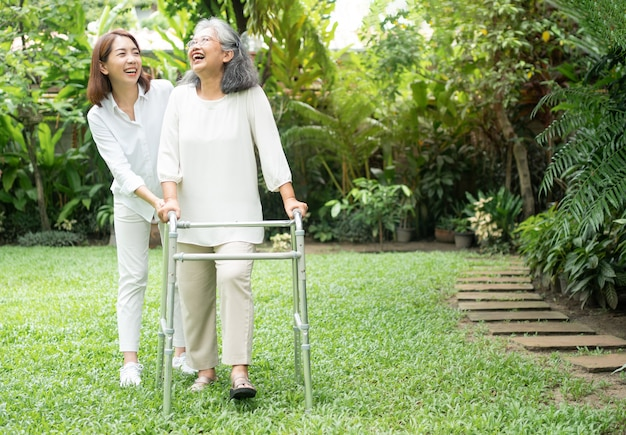 An old elderly asian woman uses a walker and walking in the backyard with her daughter