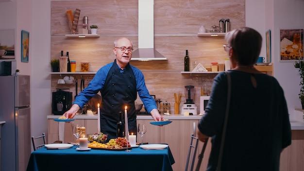부엌에서 기다리는 낭만적인 저녁 식사를 위해 아내를 위해 요리하는 노인. 나이 든 노부부는 부엌 식탁에 앉아 건강식으로 기념일을 축하하며 식사를 즐기고 있다
