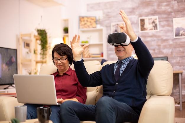 Старый пожилой пенсионер, использующий гарнитуру виртуальной реальности vr в своей уютной квартире.