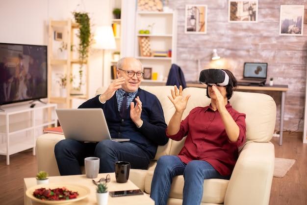 Пожилая пенсионерка в возрасте 60 лет впервые испытывает виртуальную реальность в своей уютной квартире