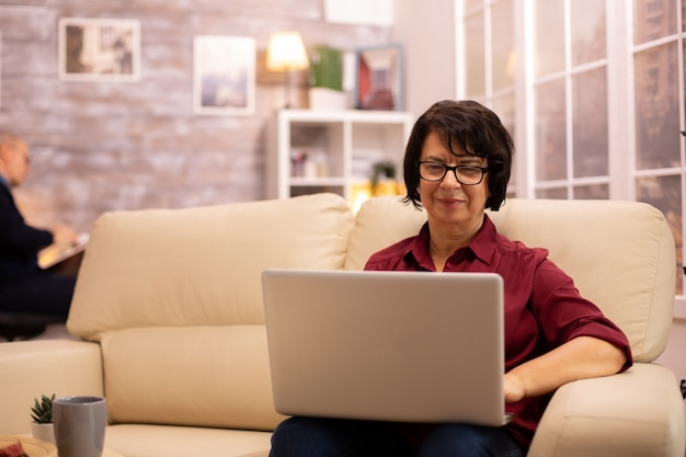 Old elderly woman on her sofa working on a modern laptop in her cozy living room. her husband is in the background