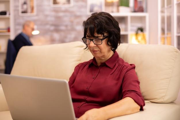 Vecchia donna anziana sul suo divano che lavora su un computer portatile moderno nel suo accogliente soggiorno. suo marito è in sottofondo