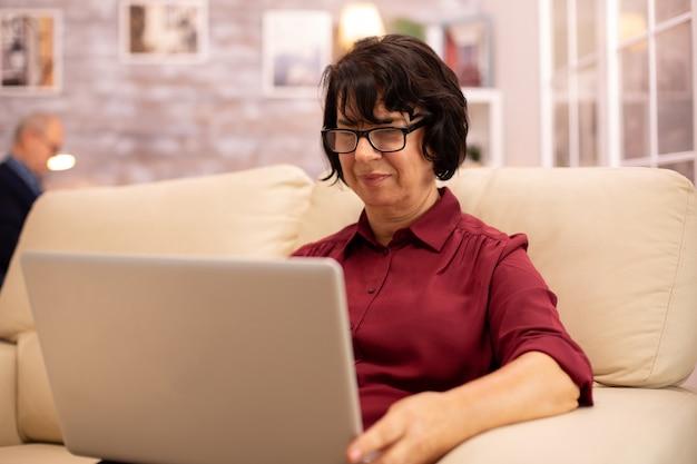 彼女の居心地の良いリビングルームでモダンなラップトップに取り組んでいる彼女のソファの上の年配の女性。彼女の夫はバックグラウンドにいます