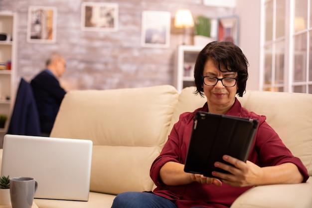 ソファに座って、居心地の良いリビングルームでデジタルタブレットpcを使用している老婆。