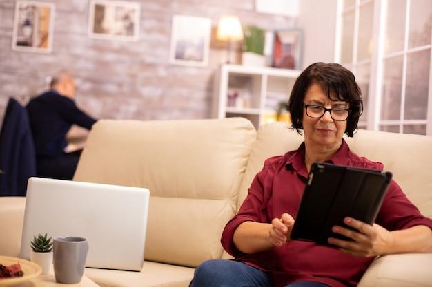 소파에 앉아 아늑한 거실에서 디지털 태블릿 pc를 사용하는 노부인.