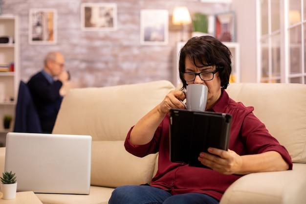 Vecchia donna anziana seduta sul divano e utilizzando un tablet pc digitale in un accogliente soggiorno.