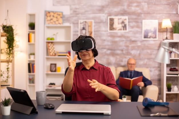 Пожилая пожилая женщина впервые в своем доме использует гарнитуру виртуальной реальности vr. концепция активных пожилых людей с использованием современных технологий