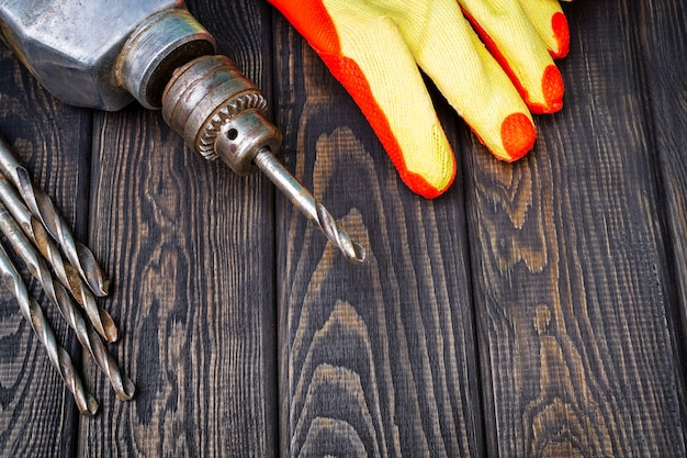 Old electric drill on dark wooden background, professional tool for the master.