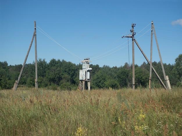 Старый электрический трансформатор в сельской местности в поле летом днем.