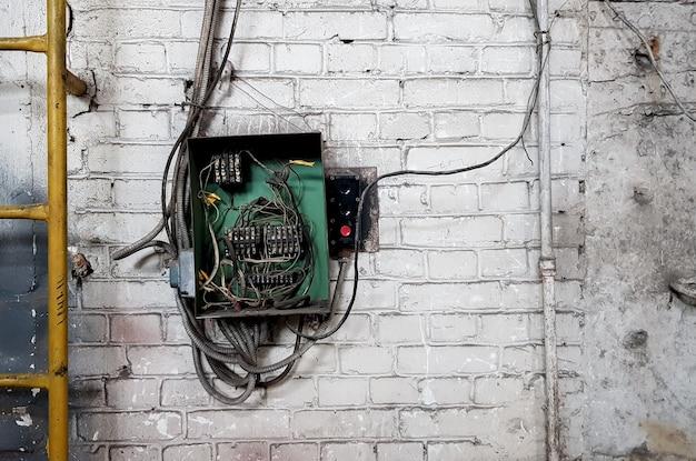 家の壁にある古い電気パネル。古い家の白いレンガの壁の電気パネルから電気ケーブルが突き出ています。