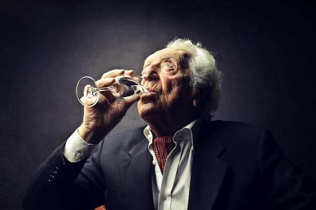 Old elegant man drinking