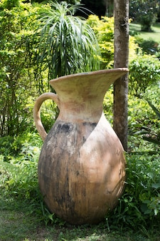 Old empty ceramics jug as a part of garden's decoration. close up full frame angle view