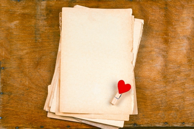 Old empty paper sheets and cloth pins with hearts  top view wooden table mock up for st valentines day card