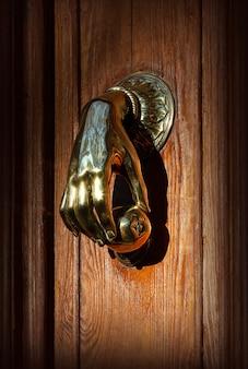 사람 손 모양의 손잡이가 있는 오래된 입구 문, 바르셀로나, 스페인