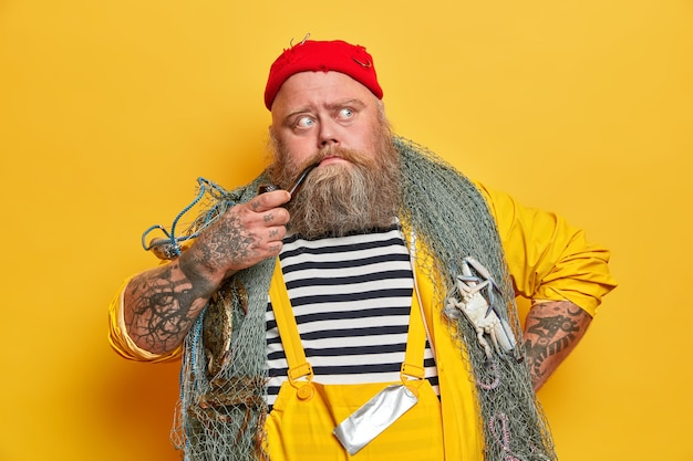 Old experienced bearded sailor thinks about next day at sea, poses with fishing gear, smokes pipe, dressed in overalls, red hat