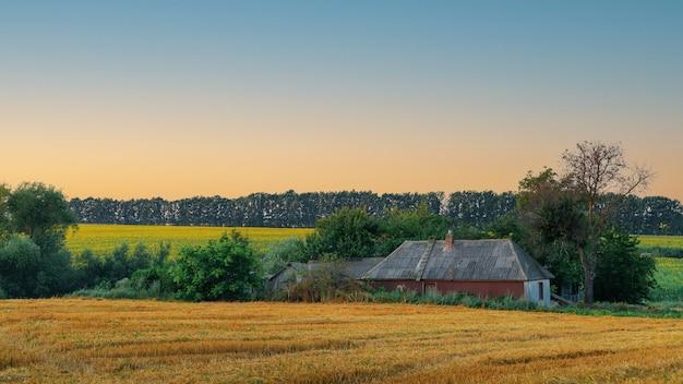 Старый дом на восходе солнца в сельской местности, скошенное поле и старый дом на спокойном фоне
