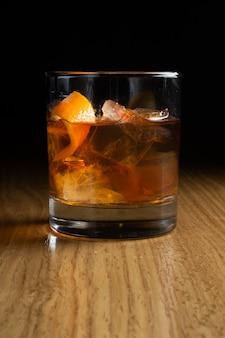 구식-버번, 스카치 또는 호밀 위스키를 바탕으로 한 알코올 칵테일로 나무 테이블에있는 투명한 유리에 오렌지 풍미로 장식되어 있습니다.