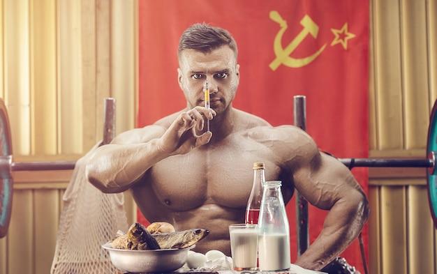 ソ連の旗で古い学校の体育館で運動をしている古いファッションのボディービルダー。 80年代のハンサムな白人スポーツマンスタイル。スポーツソビエトライフスタイル。ソ連と80年代のコンセプト