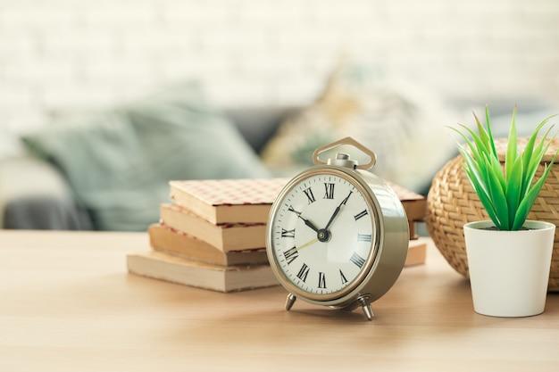 木製のテーブルの昔ながらの目覚まし時計と観葉植物