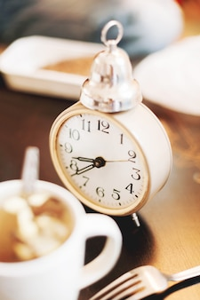 Old fashioned alarm clock and a cup of coffee. time for lunch.