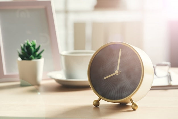 Old-fashioned alarm clock and house plant on wooden table