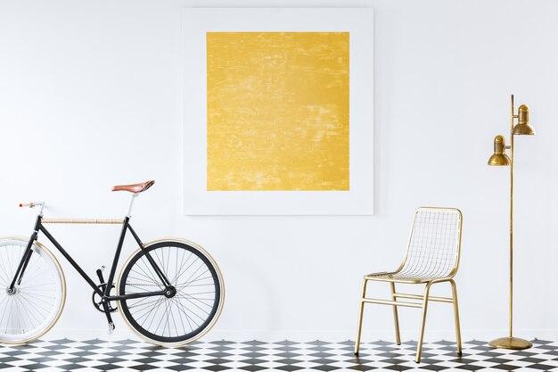황금 장식과 흰 벽에 추상 유화가있는 미니멀리스트, 힙 스터 거실 인테리어의 구식 자전거