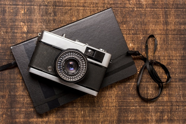 An old-fashioned camera over the closed diary on wooden desk