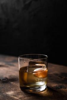Старомодный коктейль в бокале с большим кубиком льда, подсветка