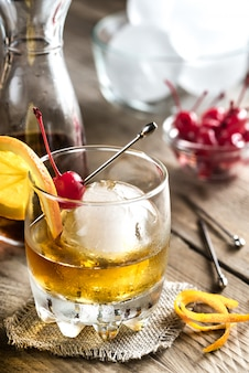 Old fashioned cocktail with cherry and orange