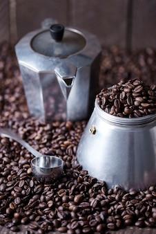 Vecchio macinino da caffè e cucchiaio tra i chicchi di caffè