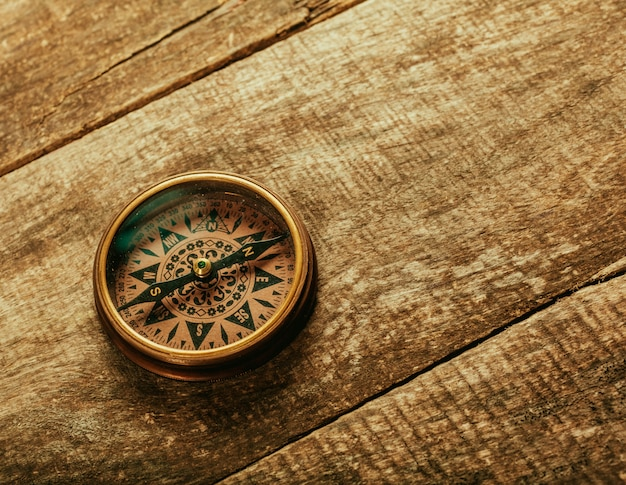 Old-fashioned compass on rustic wooden table
