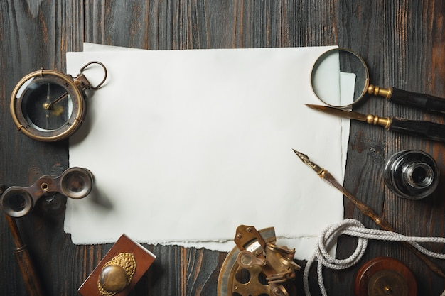 Old fashioned flat lay with letters writing accessories on dark wooden background. white sheets, pen, signet, package, ink. vintage style, steampunk, gaslight concept. magnifying glass and compass.