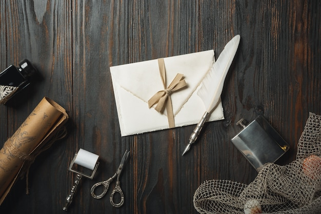 Old fashioned flat lay with letters writing accessories on dark wooden table
