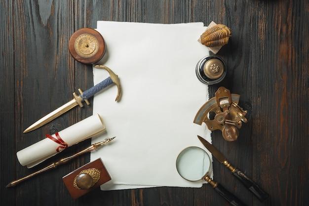 ダークウッドの背景にアクセサリーを書く手紙で昔ながらのフラット横たわっていた。白いシーツ、ペン、シグネット、パッケージ、インク。ヴィンテージスタイル、スチームパンク、ガス灯のコンセプト。虫眼鏡とコンパス。