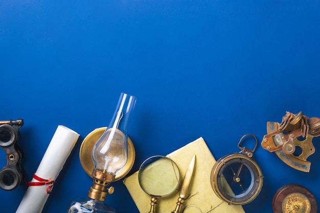 Old fashioned flat lay with retro travel, vacation accessories on blue wall.