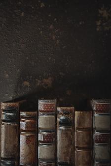 어두운 벽에 골동품 가죽 바인딩 된 책의 스택과 함께 구식 플랫 누워. 문학, 독서, 교육 개념. 레트로, 빈티지 스타일. 귀하의 광고를위한 copyspace입니다. 골동품 아카이브.