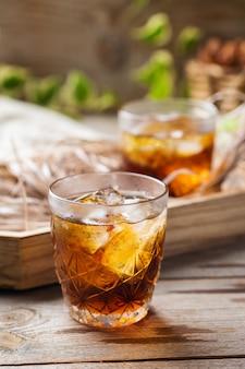 Старомодный итальянский коктейль негрони с сухим джином, кампари, вермутом мартини россо и льдом на деревянном столе. летний освежающий напиток