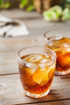 Old fashioned italian cocktail negroni with dry gin, campari, martini rosso vermouth and ice on a wooden table. summer refreshing beverage