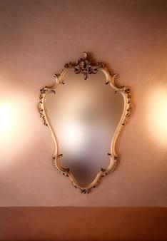Старомодное роскошное зеркало в золотой раме античного дизайна, висящее на винтажной стене