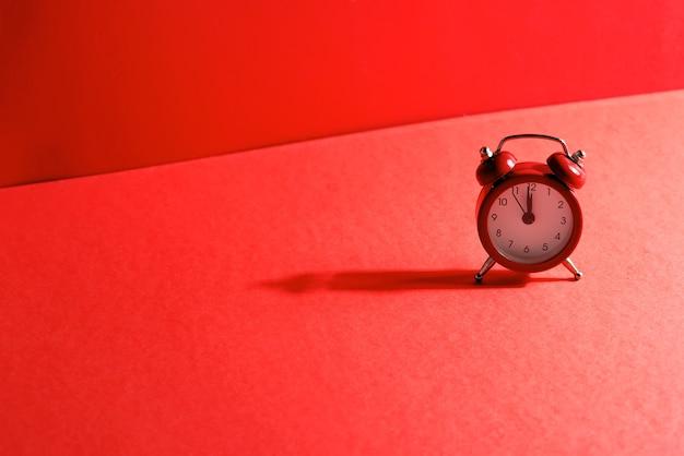 赤い色の12時の時間に矢印が付いた昔ながらのレトロな目覚まし時計