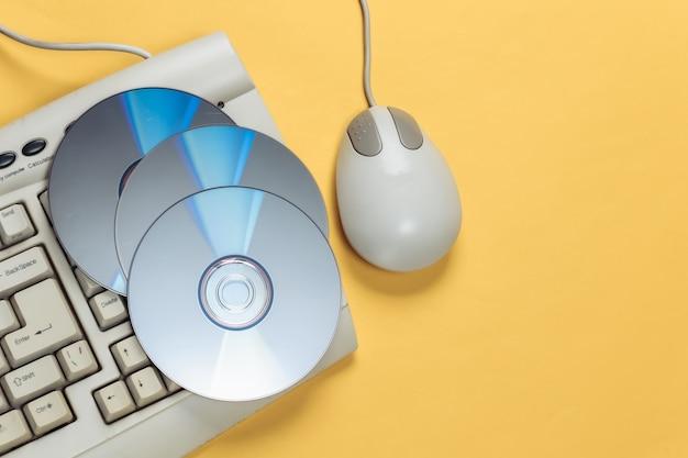 昔ながらのレトロなキーボード cd と黄色の pc マウス