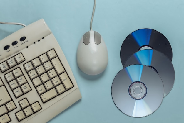 Old-fashioned retro keyboard cd's and pc mouse on blue pastel