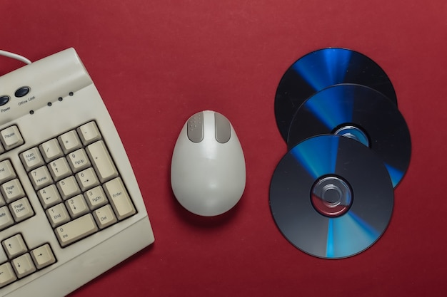 Old-fashioned retro keyboard cd's and pc mouse on red