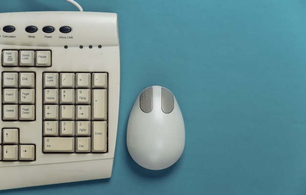 Old-fashioned retro keyboard and pc mouse on blue.