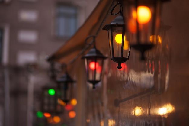 Старомодный уличный фонарь в ночное время. ярко освещенные уличные фонари на закате. декоративные светильники. волшебная лампа с теплым желтым светом в городских сумерках