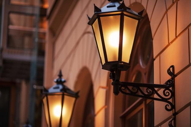 昔ながらの街路灯。夕暮れ時に街灯を明るく点灯。装飾ランプ。街の夕暮れに暖かい黄色の光の魔法のランプ