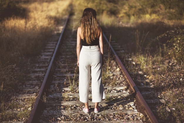 구식 스타일 사진. 기차 트랙에 서있는 여자의 후면 모습.