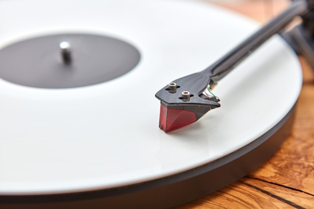 Old-fashioned turnable record player on a wooden.